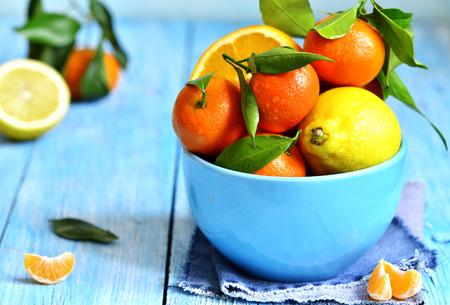 frutas tropicales: Mandarinas con las hojas verdes en un jeans servilleta en una mesa de madera azul. Foto de archivo