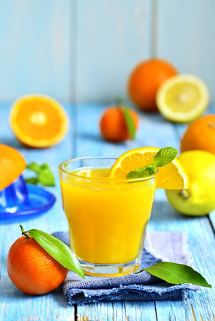 orange peel clove: Fresh citrus juice in a glass on a blue wooden table. Stock Photo
