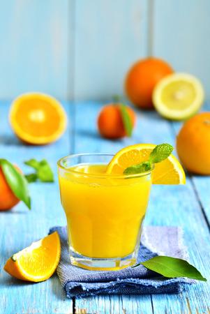 orange peel clove: Succo di agrumi fresco in un bicchiere su un tavolo di legno blu.