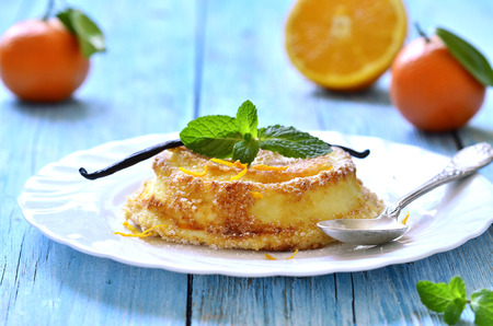 Curd souffle with orange and vanilla on a wooden table. photo