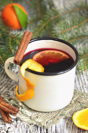 mulled wine spice: Mulled wine with orange and spice in enamel mug.