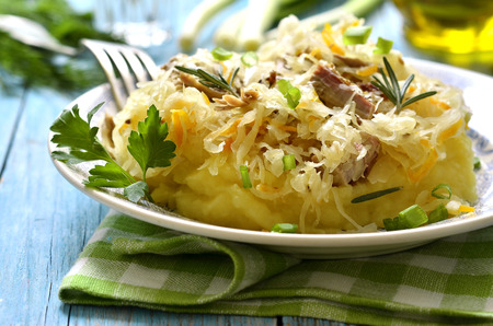 prepared potato: Potato puree garnished with sour cabbage stewed with smoked pig.Traditional german dish. Stock Photo