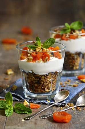 Dessert from granola,yogurt,nuts and dried apricot in a glass. photo