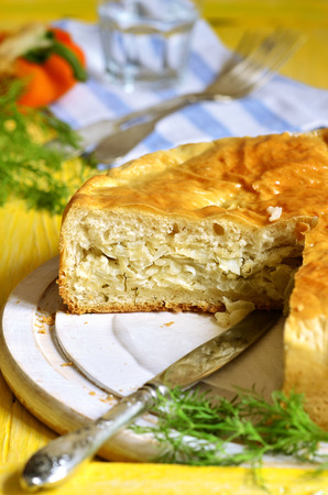 meatless: Traditional russian yeast pie with cabbage and dill on yellow background..