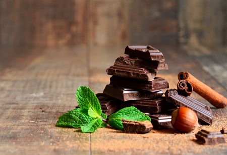 Stack of chocolate slices with mint leaf,hazelnut and cinnamon on a wooden table. Фото со стока