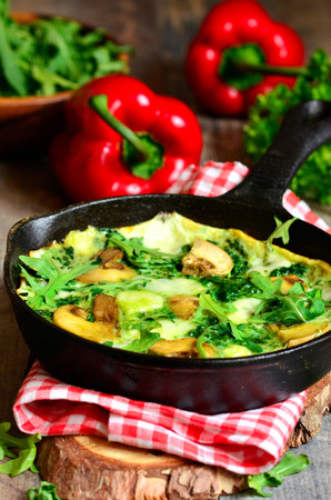 meatless: Omelet with mushrooms,cheese,spinach and arugula in a frying pan.