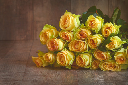 Yellow roses on a wooden background.Tinted photo. photo