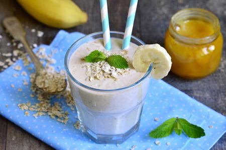 banane: Banana smoothie avec du miel et de l'avoine sur une table en bois.