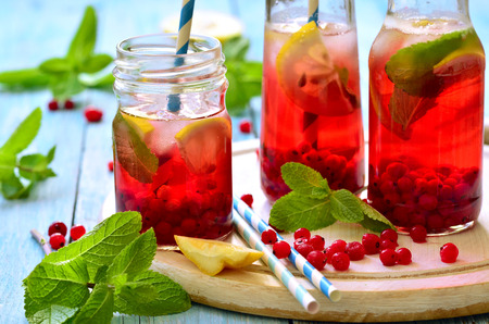 fruit in water: Cold redcurrant tea with lemon and mint in a glass jar. Stock Photo