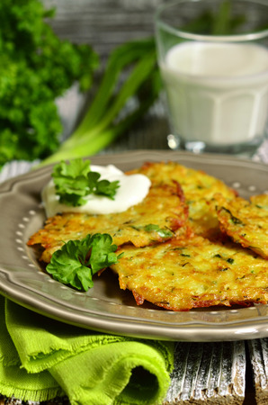 Potato fritters with cheese, green onion and herbs on rustic background. photo