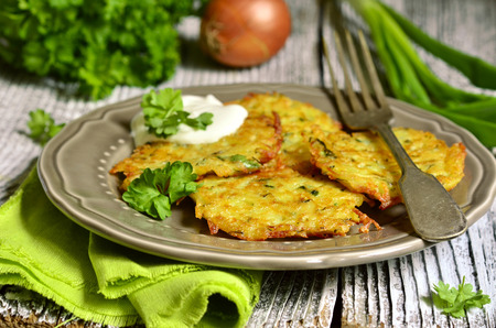 Potato fritters with cheese ,green onion and herbs on rustic background.