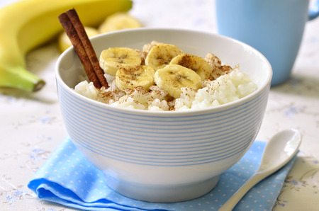 baby rice: Milk rice porridge with banana,cinnamon and honey - healthy breakfast.