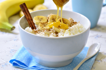 bowl with rice: Milk rice porridge with banana,cinnamon and honey - healthy breakfast.