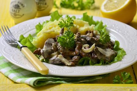 Rinderleber gedünstet mit Pilzen und Zwiebel in eine saure Sahne, garniert mit Kartoffelpüree. Standard-Bild - 40106108