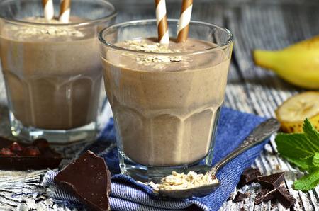 smoothies: Chocolate y plátano batido con avena en un vaso sobre la mesa de madera. Foto de archivo