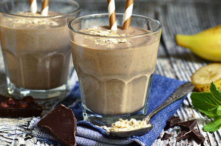 Chocolate and banana smoothie with oats in a glass on wooden table. Standard-Bild