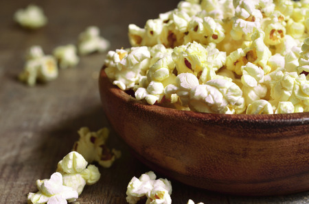 popcorn kernel: A bowl of popcorn on a wooden table.