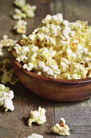 cuisine entertainment: A bowl of popcorn on a wooden table.