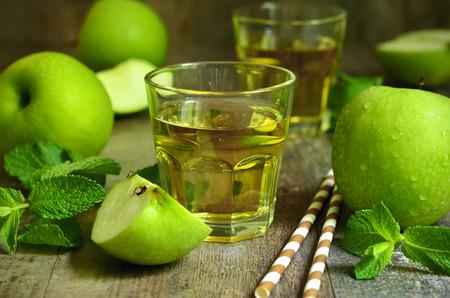 vaso de jugo: Jugo de manzana fresca en un vaso sobre la mesa de madera.