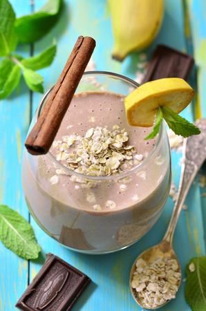 licuado de platano: Pl�tano y batido de chocolate en un vaso sobre una mesa de madera azul.