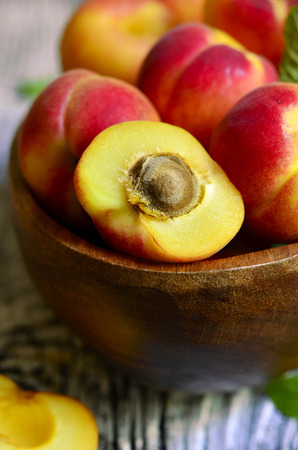 apricot kernels: Ripe red apricots in a wooden bowl with mint leaf. Stock Photo