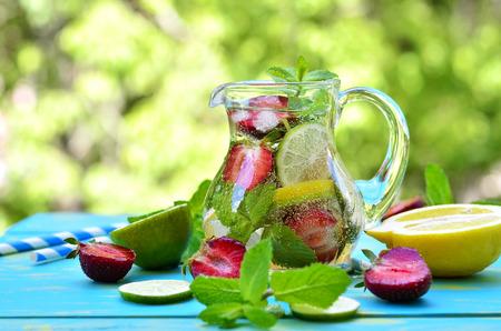 Fruitlimonade met aardbei in een waterkruik op blauwe houten lijst. Stockfoto