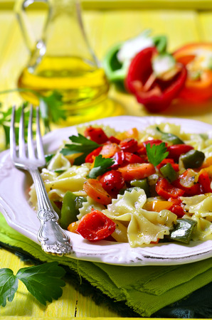 meatless: Farfalle with vegetable on a yellow wooden table.
