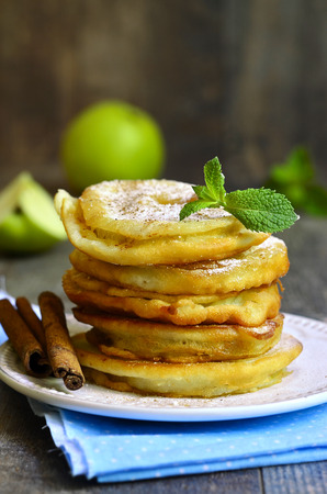 batter: Apples fried in a batter on wooden table.
