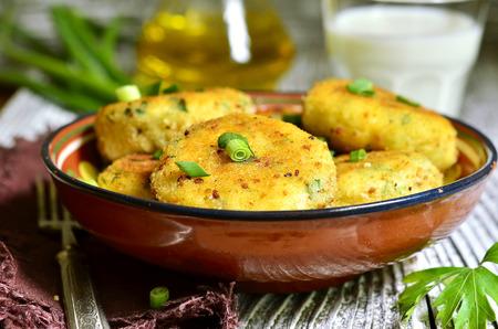 potato cod: Homemade potato patties with herbs and green onion on rustic background.