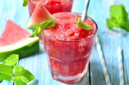Watermelon smoothie in a glass on a blue wooden table.