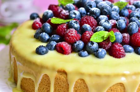 glaze: Berry cake with white chocolate glaze on a plate.
