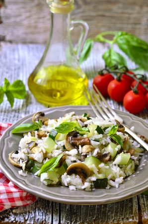 Rice with fried zucchini and mushroom on rustic background. Фото со стока