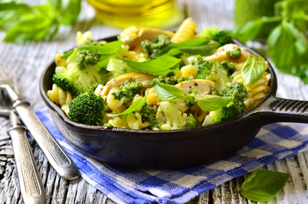 Fusilli with chicken,broccoli and basil pesto in a skillet pan.