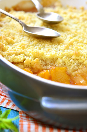 to crumble: Peach crumble on a blue wooden table.