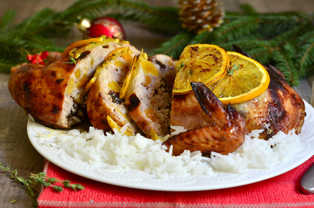 Grilled chicken stuffed with dried fruits in honey and orange glaze on festive background.
