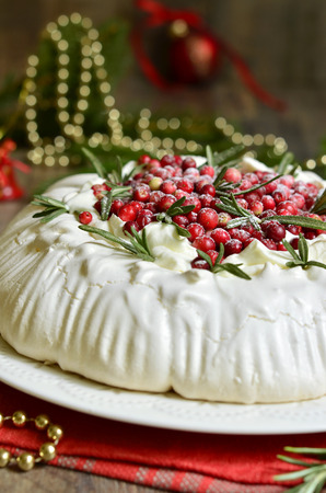christmas cake pavlova with cranberry decorated with rosemary leaves