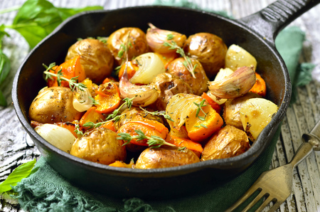 Autumn vegetable roast with herbs in a skillet pan.