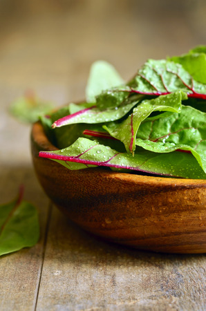 chard: Chard leaves in a wooden bowl.Rustic style. Stock Photo