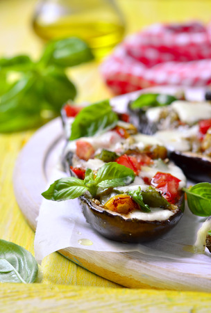 parmezan: Baked eggplants stuffed with vegetable and mozzarella on yellow wooden table.