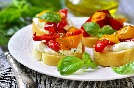 rustic food: Toasts with brynza and grilled sweet pepper on a white plate. Stock Photo