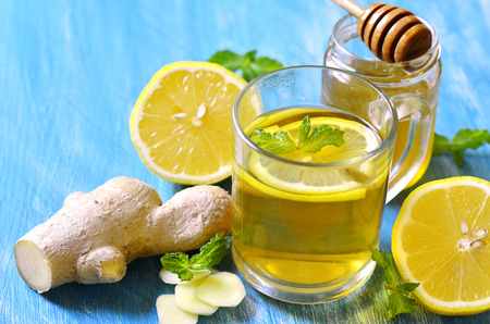 catarrh: Hot tea with ginger,lemon,honey and mint in a glass on a blue table.