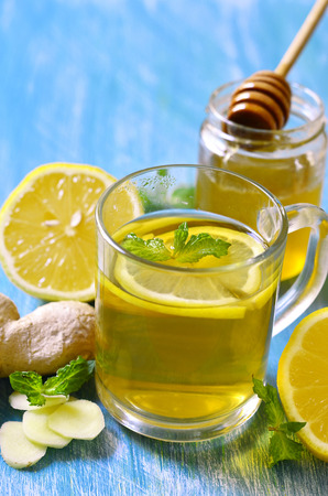 warming therapy: Hot tea with ginger,lemon,honey and mint in a glass on a blue table.