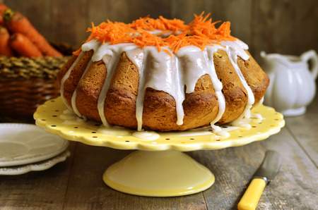 Carrot cake with sugar glaze on rustic background.