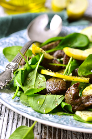 pain: Baby spinach salad with beef liver and apple on vintage plate.