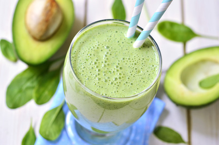 bananas: Avocado and spinach green smoothie ona light wooden table. Stock Photo