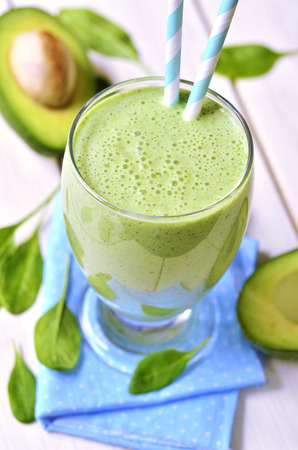 Avocado en spinazie groene smoothie ona lichte houten tafel. Stockfoto