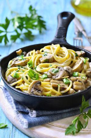 lunch meal: Spaghetti with mushroom and green onion in cream on turquoise wooden table.