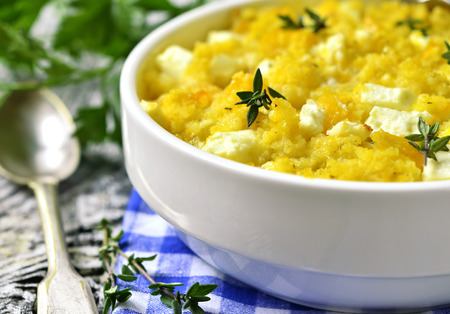 Spicy millet casserole with pumpkin and feta on wooden table.