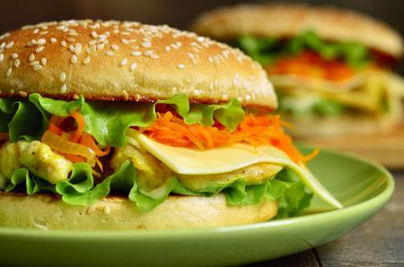 comida chatarra: hamburguesa casera de pollo, queso picante una zanahoria en una placa verde.