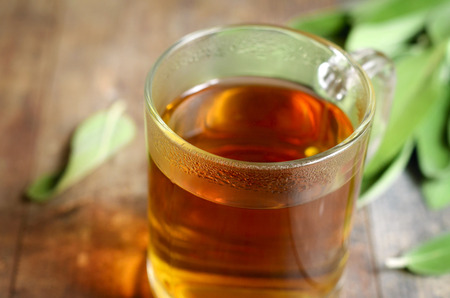 warming therapy: Tea with sage in a glass on rustic background. Stock Photo
